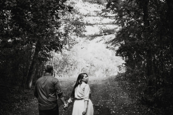 a black and white of a couple walking in a park
