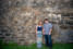 a quiet couple standing by a big stone wall